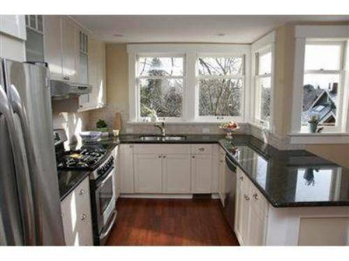 granite countertops with black cabinets. l shaped kitchen with